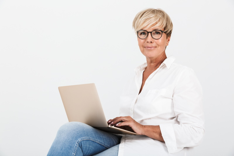 Image of pleased adult woman wearing eyeglasses smiling while sitting with laptop computer isolated over white background in studio